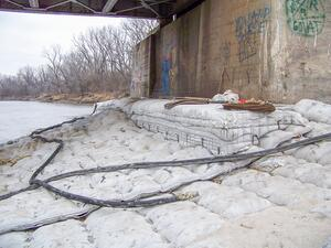 An AB mat extends out from a bridge - one of the most commonly overlooked types of structures when it comes to scour.