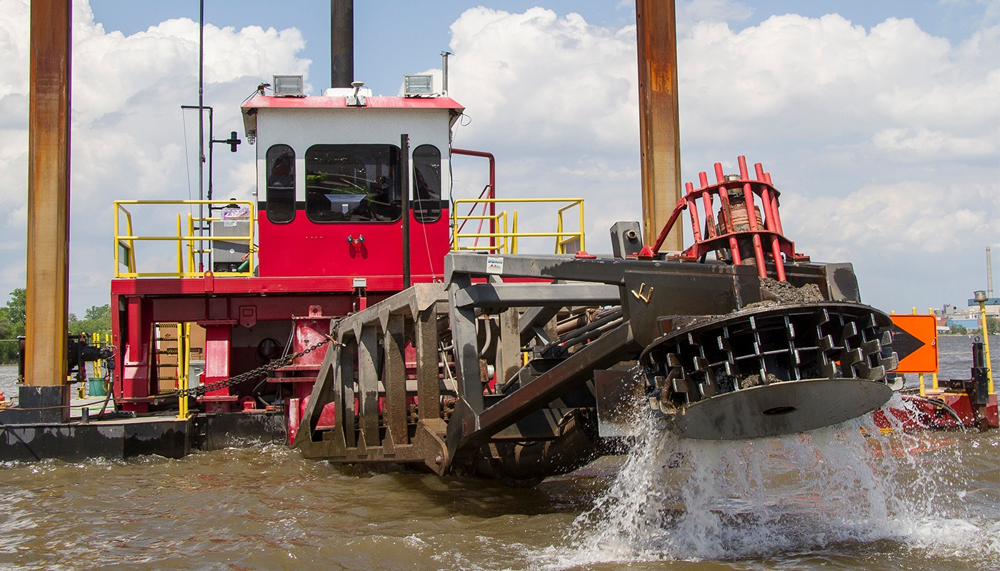 A dredge operator uses equipment to excavate and maintain waterways.