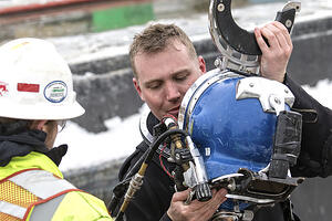 Accredited under ice diver reviewing equipment and helmet before dive