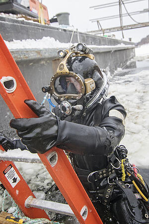 Under ice diver emerging from frozen water