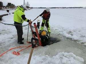 The Brennan team helps a diver into the water in Superior